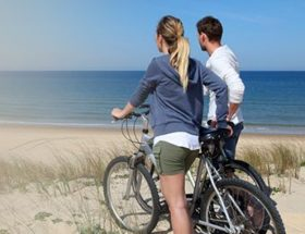 couple with bike at the beach