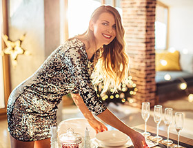 Beautiful mature woman in sparkly party dress getting the table ready