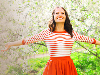 Woman standing in front of blossom trees, smiling into the sun