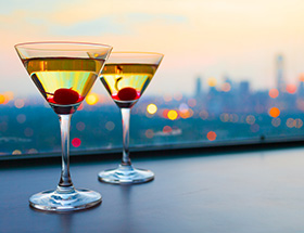Two cocktails in martini glasses with maraschino cherries