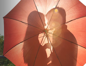 couple kissing behind red umbrella
