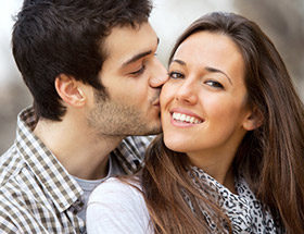 man kissing a smiling woman on the cheek