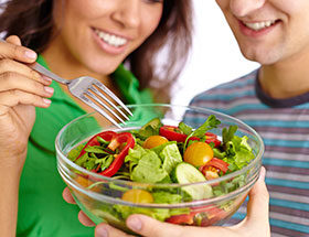 couple holding a salad