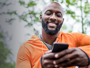 man on smartphone laughing at best opening lines for online dating