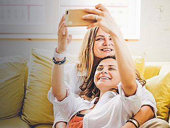 lesbian couple taking selfie on the sofa after reading advice on how to get a girlfriend as a girl