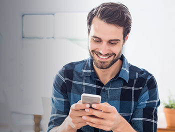 Happy gay man sending gay text messages on his smartphone
